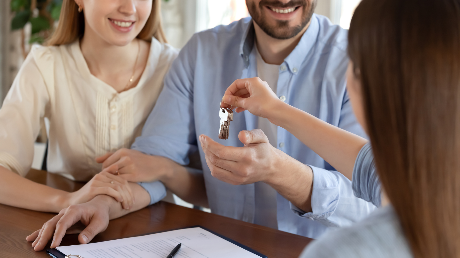 Real Estate Agent giving keys to the buyers